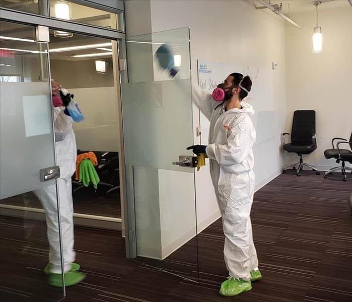Two SERVPRO employees cleaning a glass door.