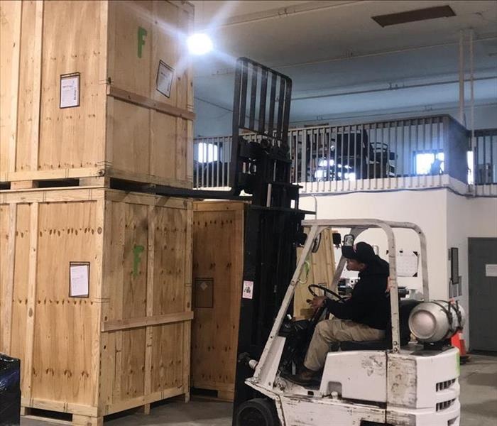Technician using forklift in warehouse
